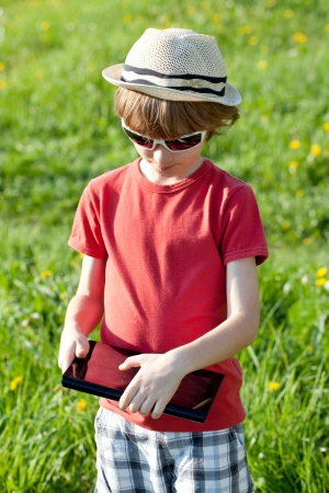 Boy with a Tablet PC in red shirt and shorts photo