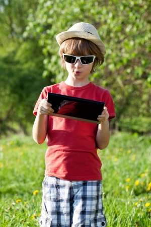 The fair-haired boy in a hat with a computer on the nature photo