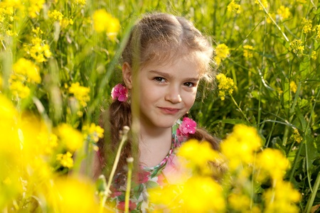 Little girl sitting in the grass and yellow flowers