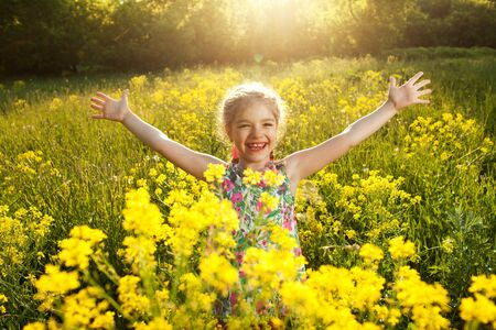 blithe: Charming little girl opened her arms among yellow wildflowers Stock Photo