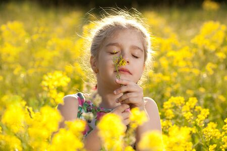 blithe: Little girl enjoys the smell of flowers in the meadow