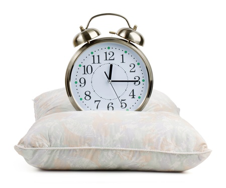 oversleep: Metal alarm clock on a pillow on  white background Stock Photo