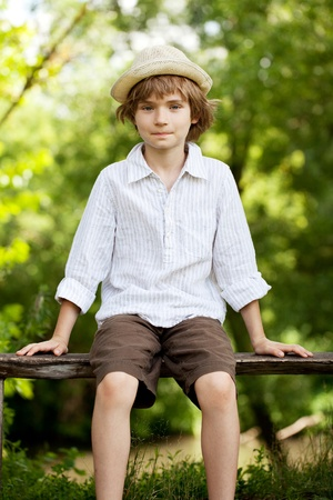 varmint: Teenager in a hat and shirt sitting on bench