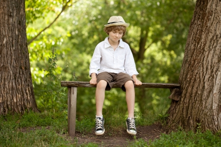 Fair-haired boy in a hat, shirt, shorts and sneakers
