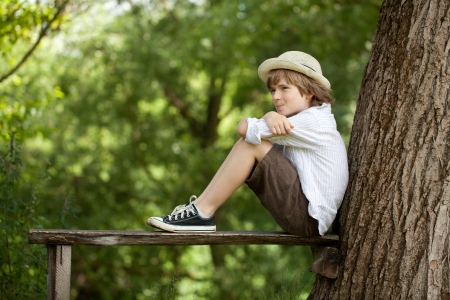 Muchacho se sienta en un banco y mira hacia otro lado Foto de archivo