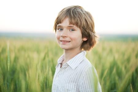 Joyful boy against a wheat field in the evening photo