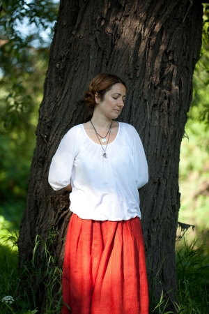 dolorous: Woman in red sarafan is sad about the tree
