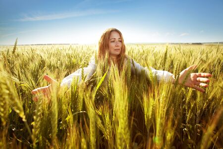 Young woman clasped her hands and ears of wheat photo