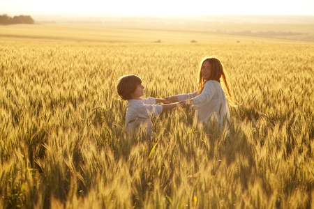 Happy mother and son are running through a wheat field in summer photo