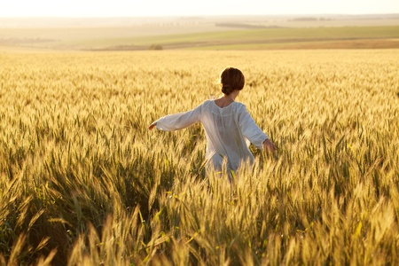 Woman in a wheat field on a summer evening