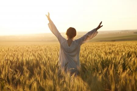 Frau mit ausgebreiteten Armen in einem Weizenfeld