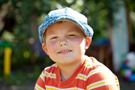 Round-faced boy in a striped t-shirt orange