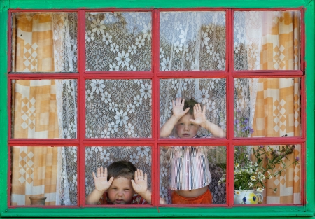 dolorous: Two unfortunate kids look out the window Stock Photo