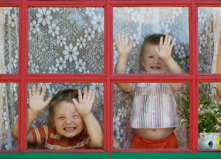 show window: Two kids fool around and show the faces at the window Stock Photo