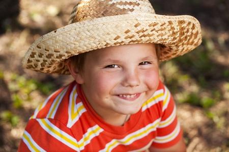 blithe: Ni�o feliz en un sombrero de paja y una camisa naranja