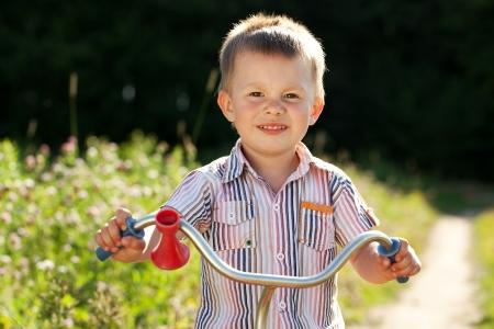 blithe: Ni�o peque�o en la camisa a rayas funciona una bicicleta Foto de archivo