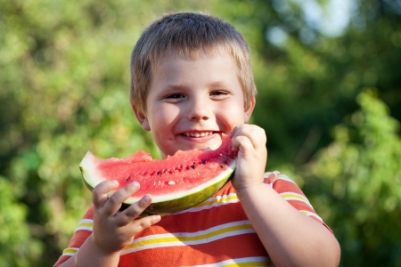 Pleased with the boy is eating a ripe watermelon photo