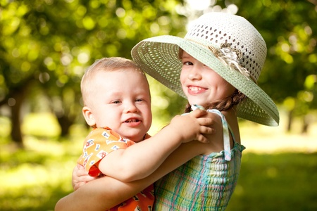 brother sister: Girl in the hat keeps the arms of his younger brother Stock Photo