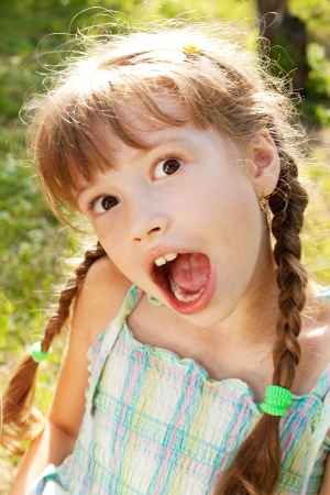 Funny girl in a dress with pigtails Stock Photo