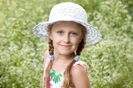 subtlety: Charming blonde girl in a hat of white wildflowers