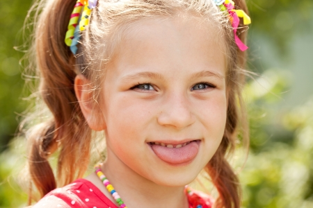 Little girl with pigtails shows off her tongue