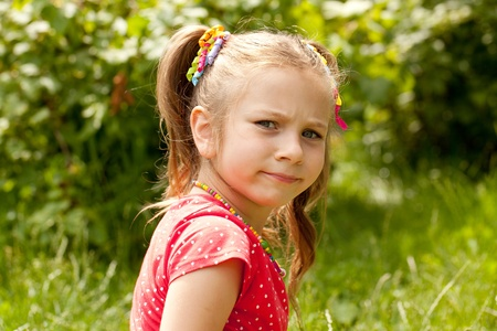 angry child: Little girl in a red blouse for someone offended Stock Photo