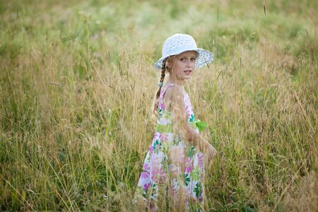 subtlety: Girl in summer dress among the tall grass Stock Photo