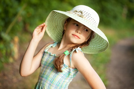 coquettish: Coquettish girl in broad-brimmed hat and a dress Stock Photo