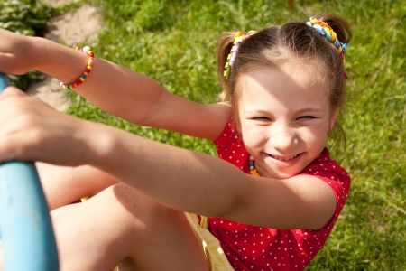 Funny little girl with pigtails plays on a sports playground photo