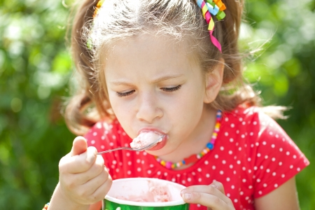 Girl in a red blouse with relish eating delicious ice cream