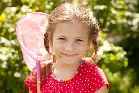 butterfly net: Smiling girl with a pink butterfly net