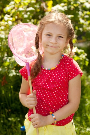 butterfly net: Smiling girl with a pink butterfly net for catching butterflies Stock Photo