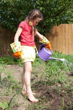 Meisje drinkinstallaties een bloembed tuin van water Stockfoto