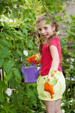 Girl taking on water in the garden watering can photo