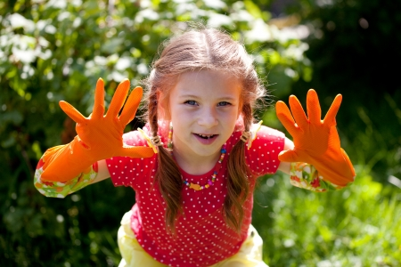 Funny girl in the orange garden gloves photo