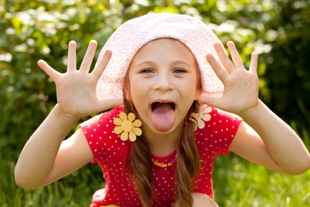 Funny little girl with pigtails shows the tongue