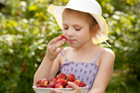 girl in the hat breathes scent of ripe strawberries photo