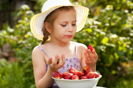 Girl in a summer hat and dress eating fresh strawberries photo