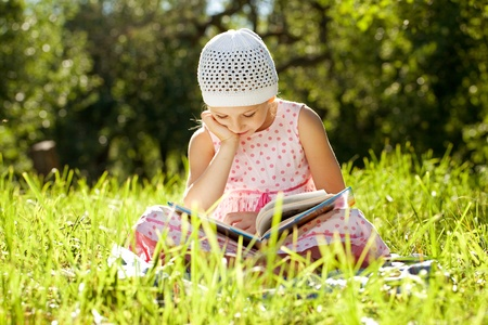 classbook: Charming girl in the hat enthusiastically reading a book Stock Photo