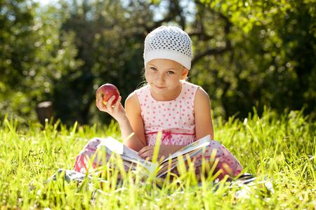 classbook: Pretty girl is reading a fascinating book and eats an apple