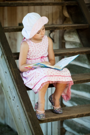 classbook: Pretty girl sitting on stairs, reading a book