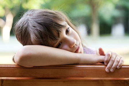 Sad cute girl sitting on a bench Stock Photo - 14882812