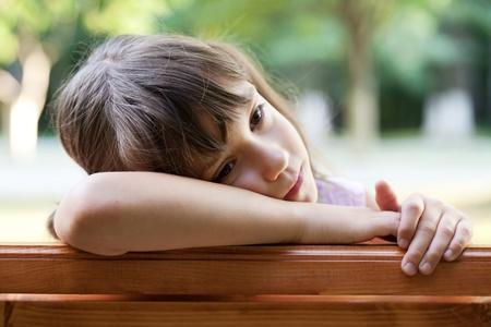 Sad cute girl sitting on a bench Stock Photo - 14882812