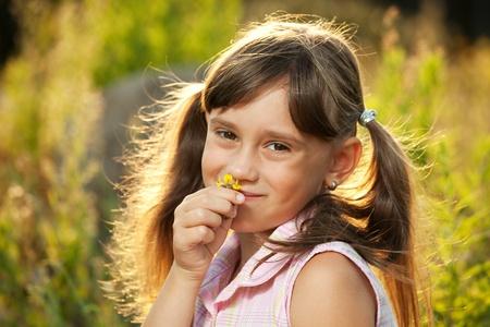 blithe: Cute little girl enjoys the smell of a flower Stock Photo