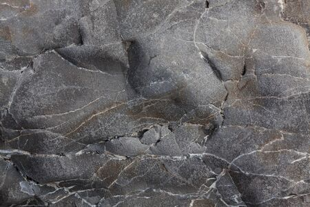 Gray smooth stone with cracks on the surface photo