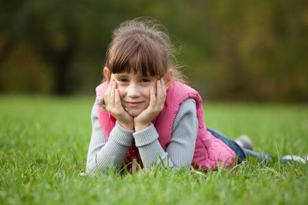 Charming little girls lying on green grass Stock Photo - 16607102