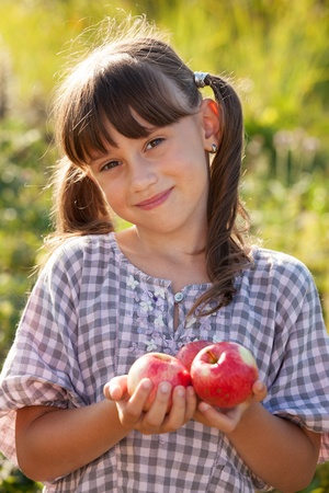 blithe: Cute little girl with ripe apple in hand