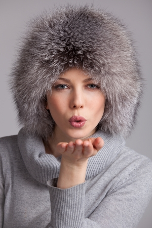Beautiful woman in a fur winter hat blowing on us Stock Photo - 17018977
