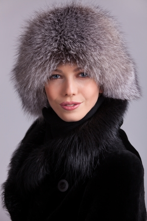 Beautiful young woman in a fur hat and coat Stock Photo - 17077338