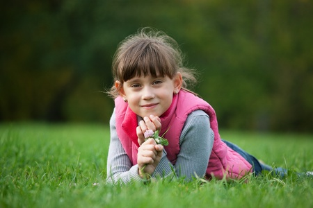 Little girl lying on the grass and holds a flower clover Stock Photo - 17276776